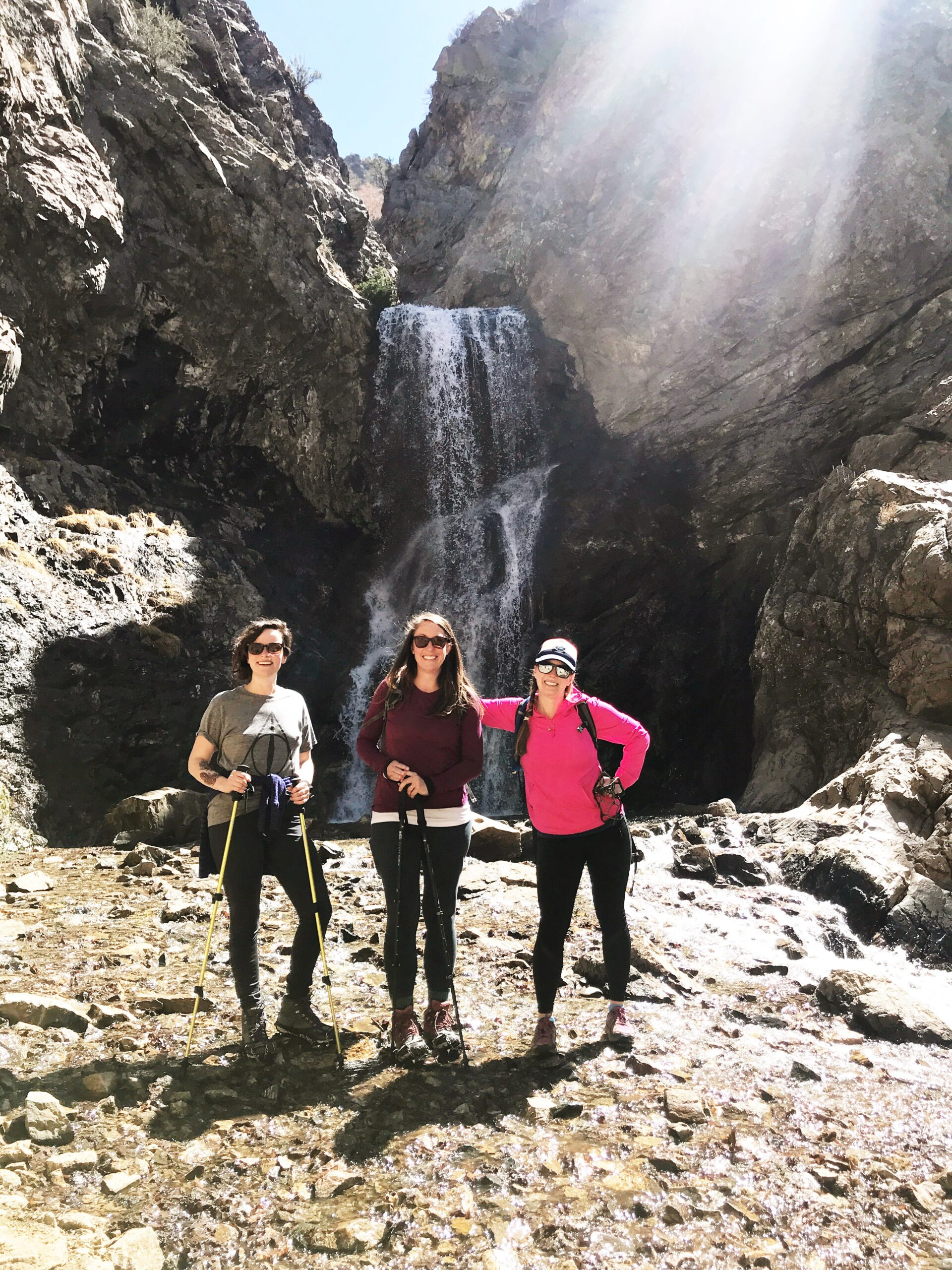 women hikers in front of a waterfall